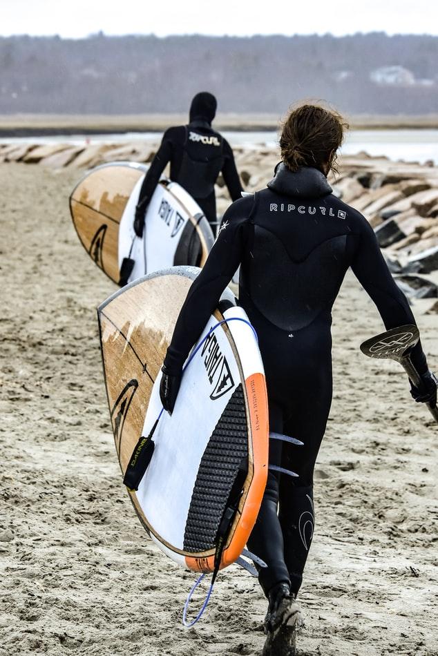 deux hommes qui vont à l'eau avec leur planche de paddle