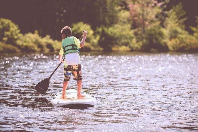 un jeune homme sur une planche de paddle